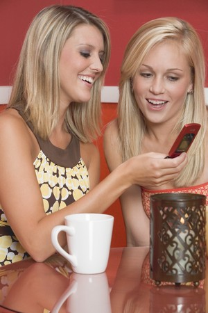 photo of object s: Two blond girls in caf� looking at mobile phone