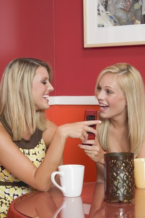 18 25 year old: Two blond girls in café with a mobile phone