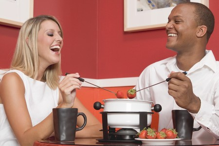 gorging: Young woman & man eating chocolate fondue with strawberries LANG_EVOIMAGES