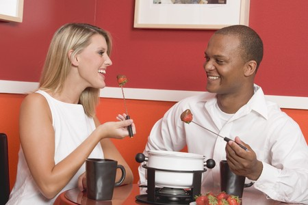 feasting: Young woman & man eating chocolate fondue with strawberries LANG_EVOIMAGES