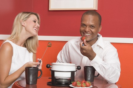 20 to 25 year olds: Young woman & man eating chocolate fondue with strawberries LANG_EVOIMAGES