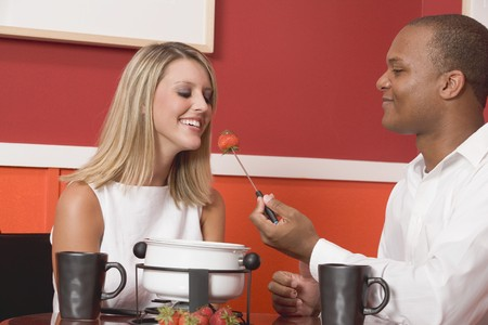 Young woman & man eating chocolate fondue with strawberries LANG_EVOIMAGES