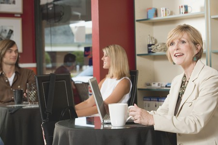 four year olds: Mature woman at laptop in a café LANG_EVOIMAGES