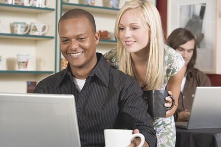 conviviality: Young woman looking at laptop over mans shoulder