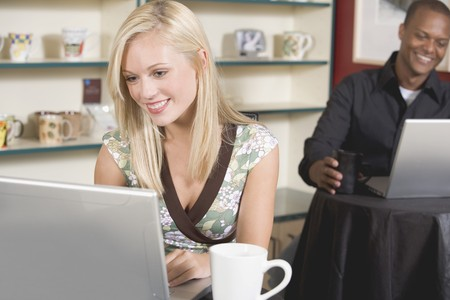 conviviality: Blond woman in front of laptop in café, man in background LANG_EVOIMAGES