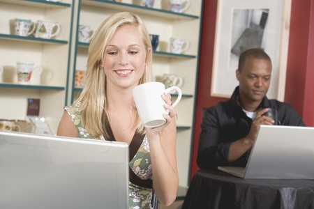 Blond woman in front of laptop in café, man in background LANG_EVOIMAGES