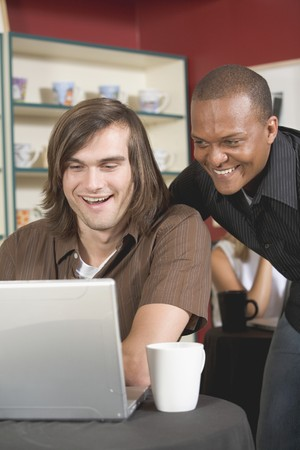 Two men in café looking at a laptop with interest