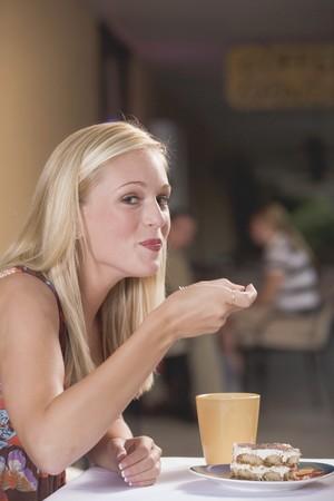 gorging: Young blond woman eating a piece of tiramisu