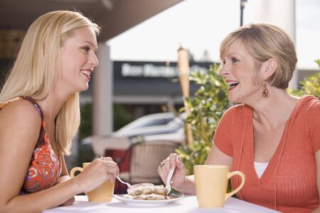 20 to 25 year olds: Two women at a street café sharing a piece of tiramisu LANG_EVOIMAGES