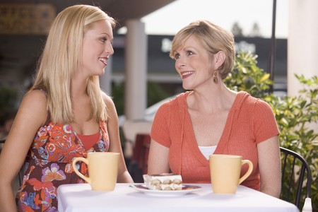30 to 40 year old: Two women in a caf� with a piece of tiramisu