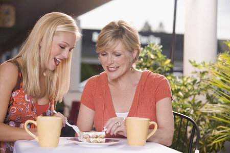 30 to 40 year old: Two women at street caf� sharing a piece of tiramisu LANG_EVOIMAGES