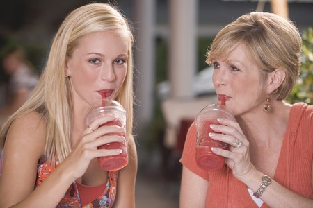 20 to 25 year olds: Young woman & mature woman drinking frozen strawberry smoothies