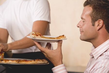 35 to 40 year olds: Man with contented expression holding slice of pizza on plate