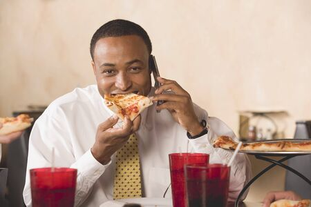 35 to 40 year olds: Businessman eating pizza & making phone call in restaurant