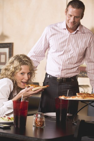 Woman in restaurant eating pizza, man just arriving LANG_EVOIMAGES