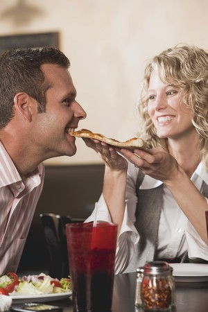 35 to 40 year olds: Woman feeding man pizza in restaurant LANG_EVOIMAGES