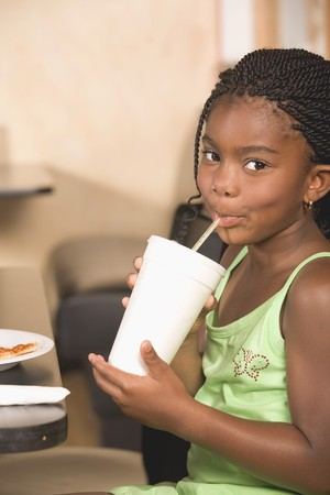 Girl in restaurant drinking a soft drink
