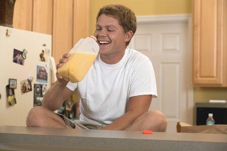 30 to 35 year olds: Man sitting in kitchen drinking orange juice LANG_EVOIMAGES