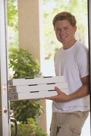 30 to 35 year olds: Man standing at house door with pizza boxes