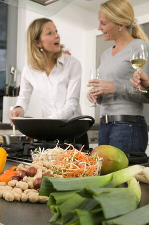 30 to 35 year olds: Women with glasses of wine chatting while preparing food LANG_EVOIMAGES