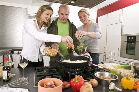 35 to 40 year olds: Man and two women cooking a stir-fry together