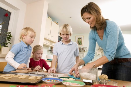 Mother and three children baking biscuits LANG_EVOIMAGES