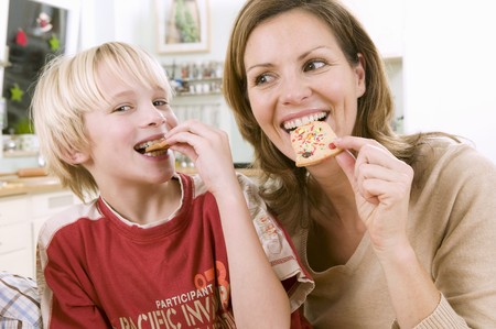 35 to 40 year olds: Mother and son eating Christmas biscuits LANG_EVOIMAGES
