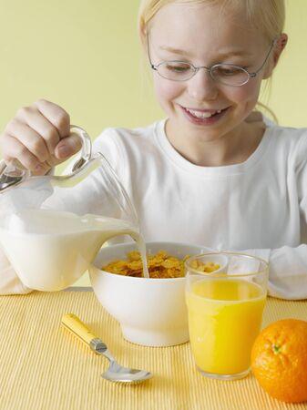 cornflakes: Girl pouring milk over cornflakes