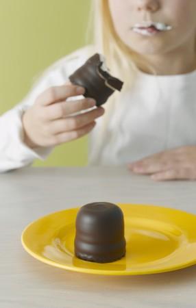 teacake: Girl eating a chocolate teacake LANG_EVOIMAGES