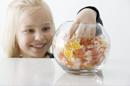 Blond girl reaching into a sweet jar LANG_EVOIMAGES
