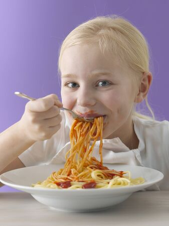 eat smeared: Blond girl eating spaghetti with tomato sauce