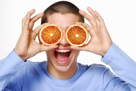 20 to 25 year olds: Young man holding two orange slices in front of his eyes