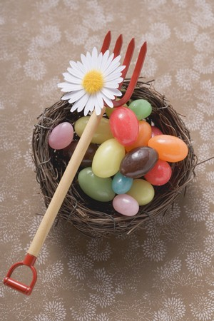 hayfork: Coloured sweets in an Easter nest with toy pitchfork LANG_EVOIMAGES