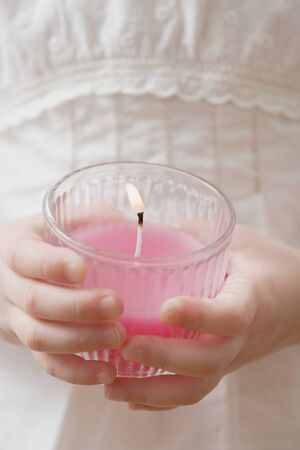 scented candle: Girl holding burning scented candle LANG_EVOIMAGES