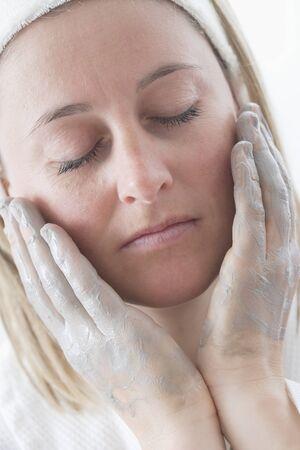 cremas faciales: Mujer joven que pone la crema en su cara