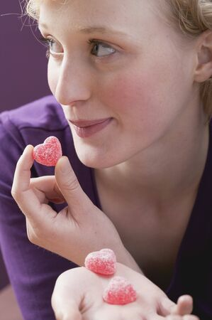 enquiring: Young woman eating sugar-coated, heart-shaped jelly sweets