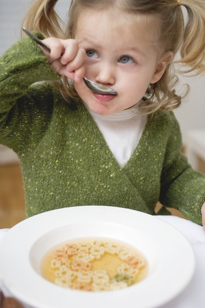 slurp: Small girl eating soup with teddy bear pasta LANG_EVOIMAGES