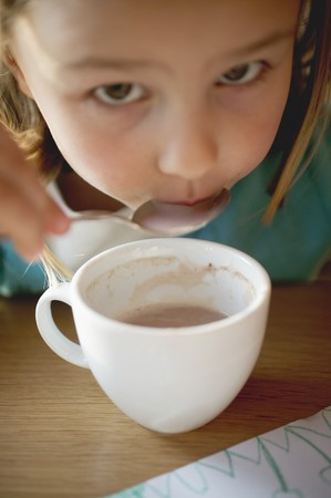 slurp: Small girl spooning cocoa out of a cup