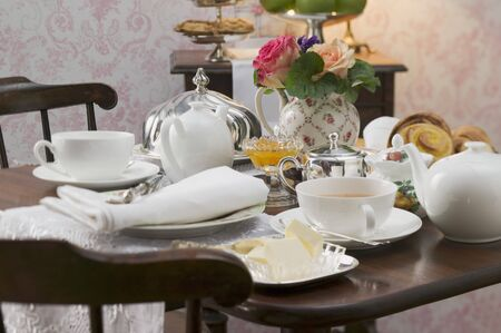 teaset: Tea things and butter dish on attractively laid table