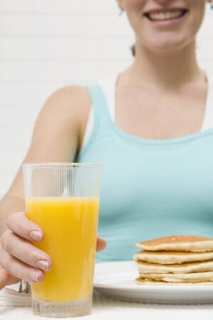 18 25 year old: Young woman with orange juice and pancakes