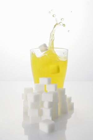 Orangeade with sugar cubes, splashing out of glass LANG_EVOIMAGES