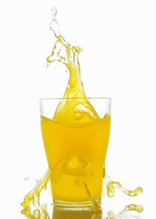 soda pops: Orangeade splashing out of a glass