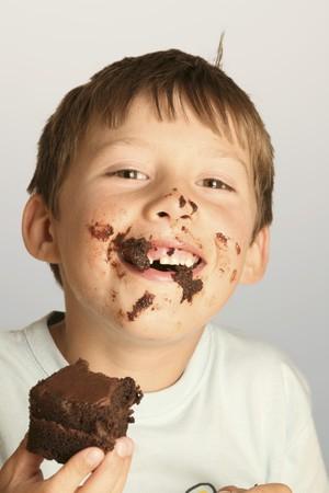 gorging: Boy eating a piece of chocolate cake