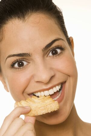 20 to 25 year olds: Young woman eating a sweet pastry