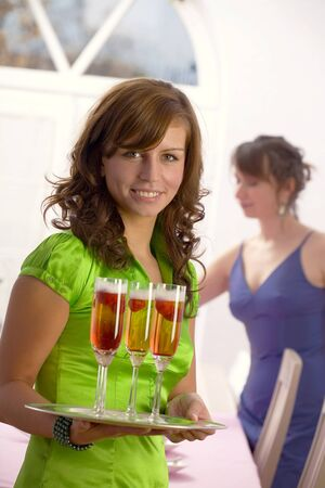 25 to 30 year olds: Young woman holding a tray of champagne and strawberries
