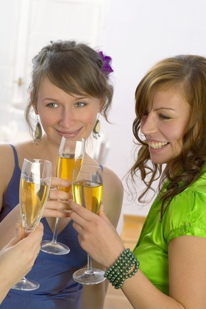 20 to 25 year olds: Young women clinking glasses of champagne