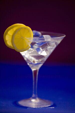 lemon slices: Un bicchiere di Martini con cubetti di ghiaccio e fette di limone LANG_EVOIMAGES