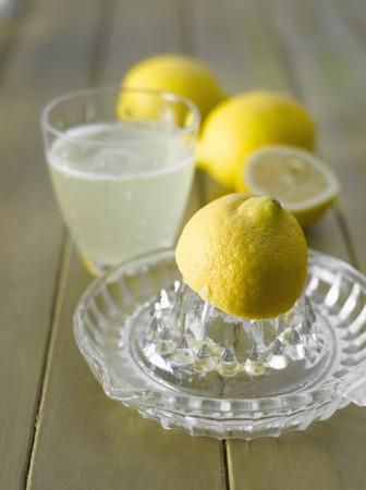 soda pops: Lemon squeezer, lemons and a glass of hot lemon