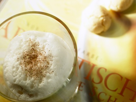 hot coffees: Caf� latte with milk foam and almond biscuits on book