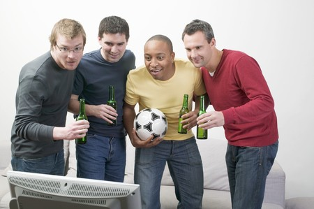 four year olds: Four men with bottles of beer and football in front of TV